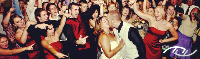 Andrew & Megan's weddings guests are cheering while they steal a kiss on the dance floor at Arroyo Trabuco Golf Club in Mission Viejo, CA. Their Wedding Entertainment Director® was Peter Merry with MERRY WEDDINGS. (Photo Credit: Jeffrey Neal Photography)