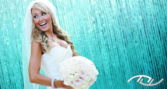 Celena smiling in her stunning bridal gown and holding her beautiful bouquet while standing in front of the blue fountain at the Surf & Sand Hotel in Laguna Beach, CA. (Photo Credit: Jim Kennedy Photographers)