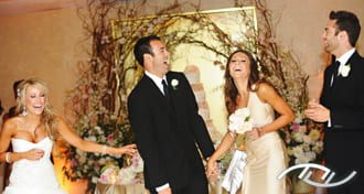 Ryan & Celena laughing during the personalized Grand Entrance introductions of their Wedding Party members delivered by their Wedding Entertainment Director®, Peter Merry with MERRY WEDDINGS, at the Surf & Sand Hotel in Laguna Beach, CA. (Photo Credit: Jim Kennedy Photographers)