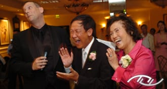 The Fun Wedding Guy, Wedding Entertainment Director® Peter Merry, eliciting laughter from the Father and Mother of the Bride at a Wedding Reception. (Photo Credit: Mike Colon Photography)